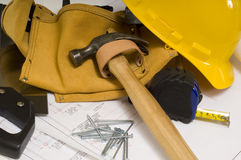 Construction or Handy Man Objects. Supplies of a construction worker or a handy man, including a hammer, tape measure, nails, tool belt and blue prints or plans Stock Photos