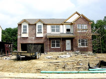 Construction - Hard Hat Area. Brick laying scaffolding surrounds a house being built in a new home community in Northern Kentucky, USA. The door sign says Hard stock photos