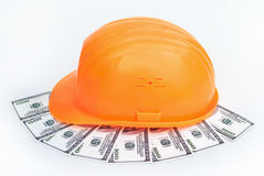 Construction hard hat and dollars. Construction hard hat on a background of dollars Stock Photo