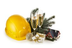 Construction hard hat, fir tree branches, model house, two glasses with champange and Christmas ornament isolated on a white. Background. New Year and Christmas stock photography