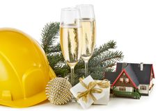 Construction hard hat, fir tree branches, model house,  two glasses with champange and Christmas ornament isolated on a white royalty free stock photo