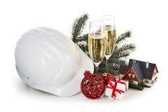 Construction hard hat, fir tree branches, model house,  two glasses with champange and Christmas ornament isolated on a white royalty free stock image