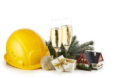 Construction hard hat, fir tree branches, model house,  two glasses with champange and Christmas ornament isolated on a white stock photography