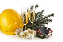 Construction hard hat, fir tree branches, model house,  two glasses with champange and Christmas ornament isolated on a white stock images