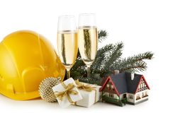 Construction hard hat, fir tree branches, model house,  two glasses with champange and Christmas ornament isolated on a white royalty free stock photography