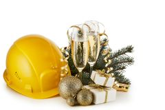 Construction hard hat, fir tree branches, two glasses with champange and Christmas ornament isolated on a white background. New royalty free stock images