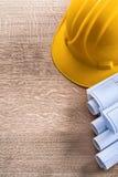 Construction helmet and blueprint rolls on wooden Stock Image