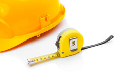 Construction helmet with measure tape on white Royalty Free Stock Photos