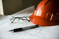 Construction helmet on the table with drawings and pencils Royalty Free Stock Photos