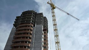 Construction of a high-rise building with a crane against a blue sky with clouds. Scene. Bottom view. grey multi-storey. Construction of a high-rise building stock footage