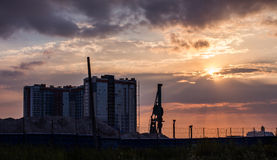 Construction. Of high-rise buildings against a beautiful sky with clouds and the setting sun in pink violet purple color late in the evening on the outskirts of Stock Photo