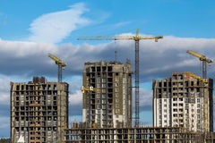 Construction of high-rise buildings with cranes. Against cloudy sky Royalty Free Stock Photography