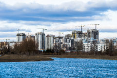 Construction of high-rise buildings with cranes on. River bank against cloudy sky Royalty Free Stock Photos