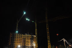 The construction of high-rise buildings at night in the spotligh Stock Image