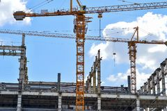 Construction of high-rise buildings, the supply of building materials with the help of a crane. The construction of high-rise buildings, the supply of building stock images