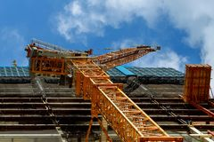 The construction of high-rise buildings, the supply of building materials with the help of a crane. The construction of high-rise buildings, the supply of royalty free stock photography