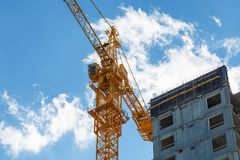Construction of high-rise panel residential building on background sky with clouds. Standing next to a tall construction. Construction of high-rise panel Royalty Free Stock Photography