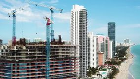 Construction of hotel with glassy walls on the background of blue sky and modern buildings ,sunny isles beach,miami. Unfinished construction of hotel with mirror stock video