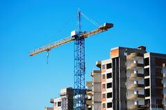 Construction of the house. The tower crane builds the house on a background of the sky Royalty Free Stock Photos