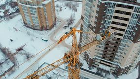 Construction of a house, aerial, copter shoot. Construction of a dwelling house in winter, high-altitude work, work of a construction crew, work of a crane stock video