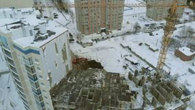 Construction of a house, aerial, copter shoot. Construction of a dwelling house in winter, high-altitude work, work of a construction crew, work of a crane stock video footage