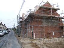 Construction of a House. The finishing of a brick house as the scaffolding is still up in the country of England Stock Photos