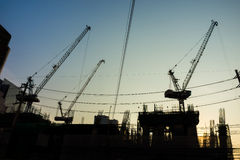 Construction industrial with construction cranes silhouette at sunset Stock Images