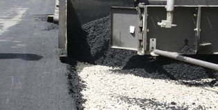 Construction. Industrial pavement truck laying fresh asphalt on construction site Royalty Free Stock Photos