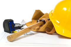 Construction Industry. Items used by a construction worker including a leather tool belt, a hammer, a tape measure, tools, floor plans and a yellow hard hat Stock Images