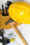 Construction Industry. Items used by a construction worker including a leather tool belt, a hammer, a tape measure, tools, floor plans and a yellow hard hat Royalty Free Stock Image