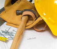 Construction Industry. Items used by a construction worker including a leather tool belt, a hammer, a tape measure, tools, floor plans and a yellow hard hat Stock Photography