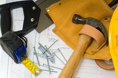 Construction Industry. Items used by a construction worker including a leather tool belt, a hammer, a tape measure, tools, floor plans and a yellow hard hat Stock Photos