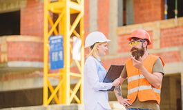 Construction industry concept. Discuss progress project. Woman engineer and bearded brutal builder discuss construction stock image