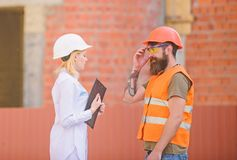 Construction industry concept. Woman engineer and bearded brutal builder discuss construction progress. Relationships stock photography