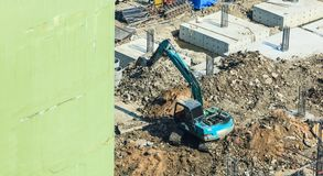 Construction Industry, Concrete building construction site. Concrete piles driven into the ground by excavator at foundation pit. Industrial Business, Working royalty free stock photos