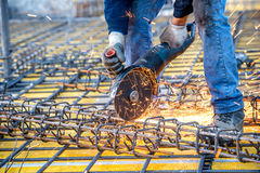 Construction industry details - worker cutting steel bars using angle grinder mitre saw. Stock Images