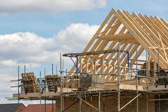 Construction industry. Timber framework of house roof trusses wi. Th scaffold on a building being built on a new housing estate royalty free stock images