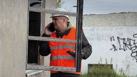 Construction inspector with cell phone near broken window stock video footage