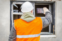 Construction inspector filming with cell phone near building Stock Photography
