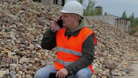 Construction inspector with phone at the pile of crushed stone stock video footage