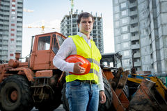 Construction inspector posing next to excavator on building site Stock Photos