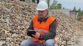 Construction inspector with tablet PC near crushed stone stock video