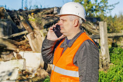 Construction inspector talking on smartphone near abandoned,damaged building Royalty Free Stock Photos