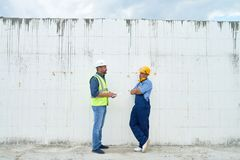 Construction Inspector Talking to Foreman. Profile view of construction inspector wearing hardhat and reflective jacket talking to young foreman and taking stock image