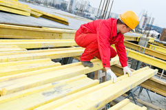 Construction installer at work. Builders rigger works with wood board installing formwork at construction site Royalty Free Stock Image