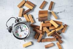 Construction Jenga tower and clock on wood tebla stock image