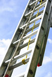 Construction ladder. Closeup of construction aluminum extension ladder against blue sky stock photography