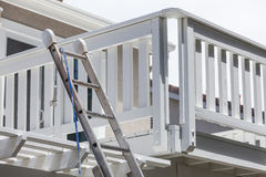 Construction Ladder and Painting Hose Leaning on House Deck Stock Photography