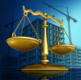 Construction Law. Concept as a justice scale over a working building site with cranes and a structure being built as a concept for architecture permits and real Stock Photography