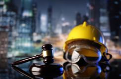 Construction law. Law theme. Construction law`s symbols  - helmet and gavel. Constuction background Royalty Free Stock Images